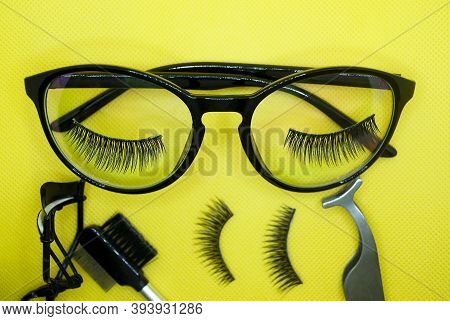 The Creative Layout Is Made Of Glasses And Eyelashes On Pastels On A Yellow Background. Fake Eyelash
