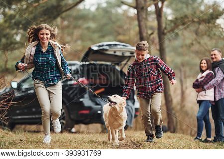 Sister And Brother Runs Forward. Happy Family Have Fun With Their Dog Near Modern Car Outdoors In Fo
