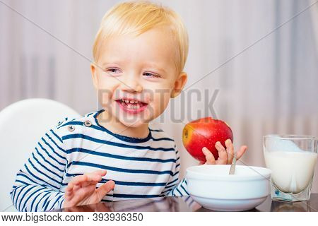 Kid Cute Boy Sit At Table With Plate And Food. Healthy Food. Boy Cute Baby Eating Breakfast. Baby Nu