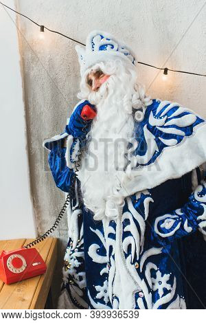 Santa Claus On The Phone At His Home Compiles The Wishlist For Christmas.