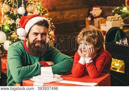 Happy Little Child Son With Father Dressed In Winter Clothing Think About Santa Near Christmas Tree.