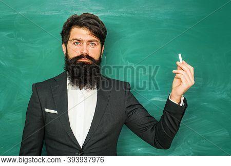 Good Teachers Enjoy Teaching. Bearded Professor At School Lesson At Desks In Classroom. Chalkboard C