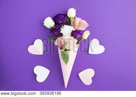 White, Pink And Violet Flowers In A Paper Pink Cone And Pink Hearts On The Violet Background Closeup