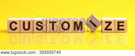 Customize Word Is Made Of Wooden Building Blocks Lying On The Yellow Table, Concept
