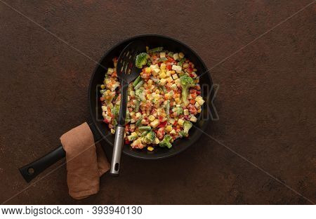 Frozen Vegetables In A Frying Pan With A Skimmer On A Brown Background. Copy Space, Top View, Flat L