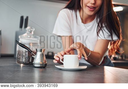 With Cup Of Fresh Coffee. Young Beautiful Brunette In Casual Clothes Indoors In Kitchen At Daytime.