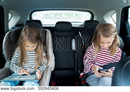 Little Girls, Sisters Are Driving In Car, Children Play Video Games In Tablet And Mobile Phone. Trav