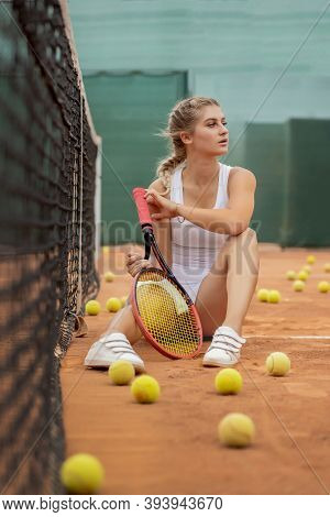Portrait Of Beautiful Young Woman Sitting Near Net In Tennis Court With Ball Outdoor. Confident Spor