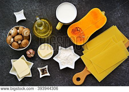 Prepared Ingredients For Cooking Lasagna With Pumpkin And Mushrooms On An Dark Concrete Background.
