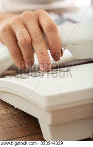 Closeup View Of Female Hand Dialing Telephone Number Using Landline Phone.