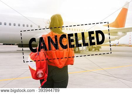 Cancellation Of Flights Due To Coronavirus. A Young Girl Traveler Stands Near The Plane. Tourist Hol