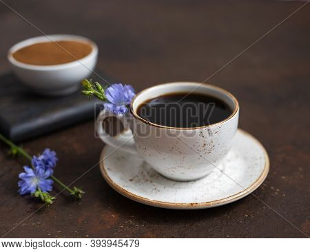 Chicory Coffee And Blue Flowers On A Dark Brown Background. Ground Chicory Root In A Bowl. Coffee Su