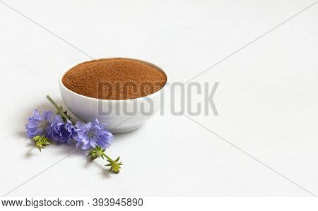 Chicory Root Powder And Blue Chicory Flower On A White Background. Natural Coffee Substitute. Cichor