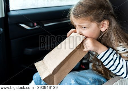 Little Girl Is Driving In Car. Kid Is Sick, Feels Bad And Vomiting Into Paper Bag. Traveling, Riding