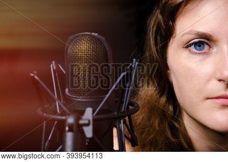 Brunette Woman For A Professional Microphone, Close-up. Professional Record Of The Singer In The Stu