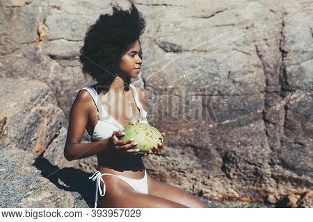 A Dazzling Young Cheerful African-american Woman In A White Swimsuit Is Sitting On The Warm Rock Of
