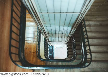 View From Above With A Shallow Depth Of Field Of A Long Stairwell Going Down In A Spiral, An Old Res