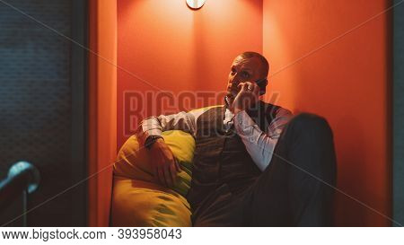 A Handsome Mature Caucasian Man Entrepreneur Is Having A Phone Conversation While Relaxing On A Soft