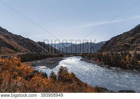 A Stunning Fall Mountain Scenery With A Blue River In The Middle Surrounded By Ridges, Yellowed Autu