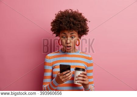 Astonished Surprised Curly Young Woman Stares At Smart Phone Display, Sees Something Amazing Online,