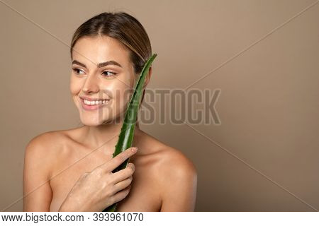 Smiling Happy Young Woman Holding Aloe Leaf In Her Hands On Beige Background. The Concept Of Skin Ca