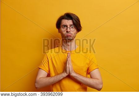 Worried Adult Man Looks Concerned And Focused At Camera, Asks For Help In Difficult Situation, Holds