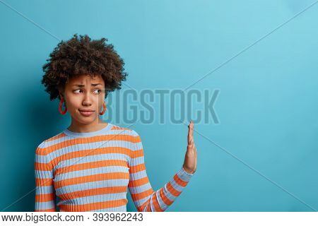 Get Away From Me. Displeased Curly Woman Pulls Hand Aside In Stop Or No Gesture, Being Bothered By S