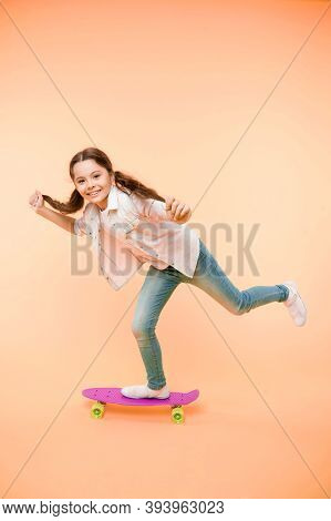 Girl Ride Penny Board Yellow Background. Kid Having Fun With Penny Board. Carefree Happy Ride. Hobby