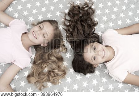 Girls With Long Curly Hair Lay On Bed Top View. Children Perfect Curly Hairstyle Looks Cute. Conditi