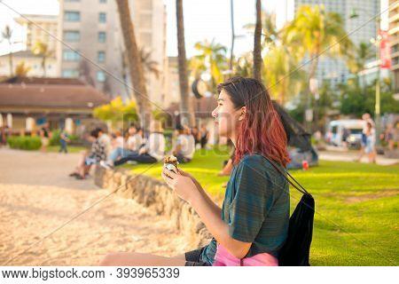 Biracial Teen Girl Sitting At Waikiki Beach Near Sunset Eating Spam Musubi With Crowd Of Tourists Bl