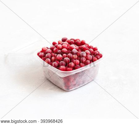 Frozen Cranberries In A Plastic Container On A White Background. Storage Of Frozen Food. Side View.