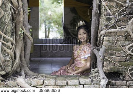 A Thai Girl In Traditional Thai Dress Sits Inside An Old Church Of An Old Thai Temple.