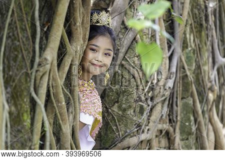 A Portrait Of A Thai Girl Wearing A Traditional Thai Dress With An Old Church Of An Old Thai Temple.