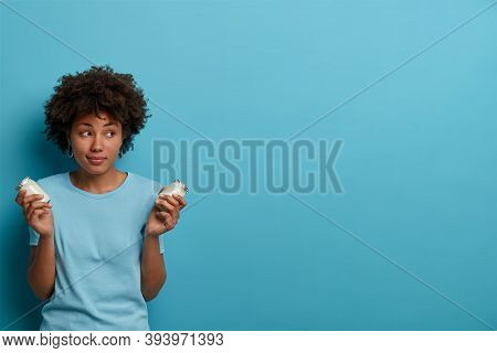 Healthy Sporty Woman With Afro Hair Holds Glass Jars Of Fresh Yoghurt, Going To Prepare Breakfast, H