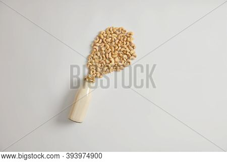 Glass Bottle Of Cold Cashew Milk Next To Pile Of Nuts On White Background. Nutrient Organic Non Diar