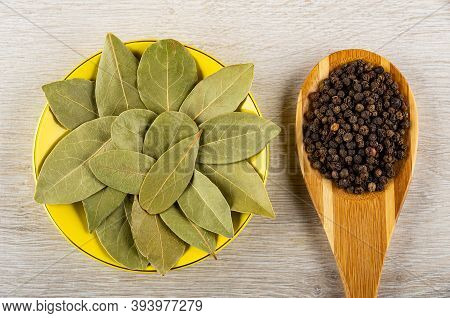 Dried Bay Leaves In Yellow Plate, Bamboo Spoon With Peppercorn On Wooden Table . Top View