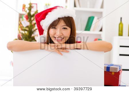 Asian Christmas woman wearing Santa hat leaning over billboard sign, indoor / inside home