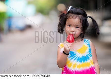 Girl Wanders For A Walk And Eating Red Stick Ice Cream. Child Wears Colorful Sleeveless Shirt. Asian