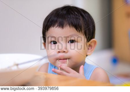A 2-year-old Child Boy Uses His Hand To Pick Up Instant Noodles. Asian Baby Boy Put A Line Of Instan