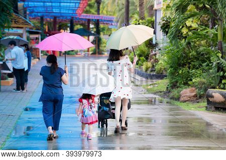 Bangkok Thailand - 19 Sep 2020. Family Walked And Holding Umbrella In Drizzle Of Rain During The Rai