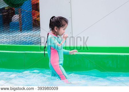 Side View Of Asian Kid Wear Swimsuit In Mint Green. Child Was Wiping Water Over Her Face After Playi