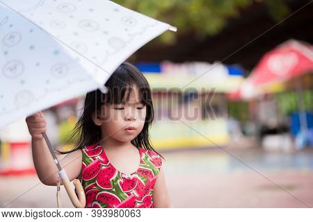 Snap Shot. Cute Girl Walking In Umbrella On A Rainy Day During The Rainy Season. Little Asian Child