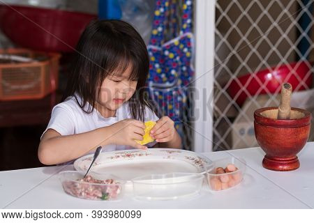 Happy Kid Girl Helped Her Family Cooking. Asian Children Are Practicing Wrapping Yellow Dumplings. C