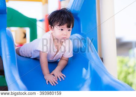 Asian Toddler Boy Was Face Down To Play On The Blue Slide. In Hot Day Child Sweats On His Face. Chil
