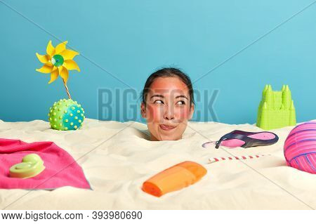 Dreamy Sly Woman Licks Lips And Thinks About Something Pleasant, Has Red Sunburned Face, Buried In S
