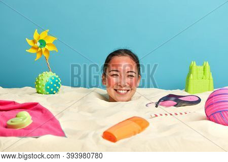 Positive Brunette Asian Woman Sticks Out Head From Sand, Has Red Skin After Getting Sunburn, Smiles