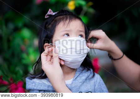 Mother's Hand Is Wearing A Medical Face Mask For Her Asian Daughter. In The Current Situation Covid-