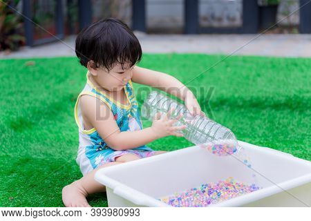 Adorable Asian Toddler Boy Playing With Sensory Water Bead. Cute Child Pours A Plastic Bottle, Pouri