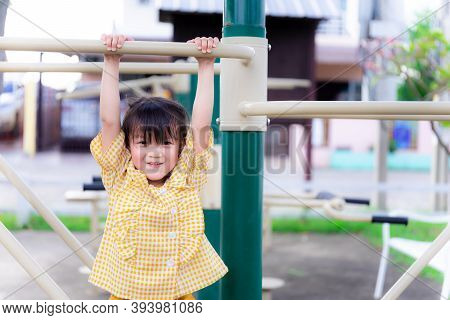 Active Little Child Girl Playing On Playground. Children Hands Holding With Workout Machine, Hung On