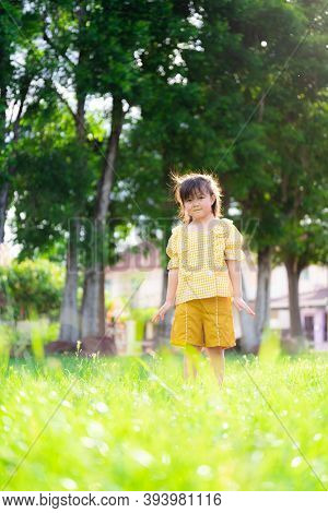 Happy Girl Is Playing In The Meadow. Child Was Wearing A Yellow Dress. Children Smiled Sweetly. The